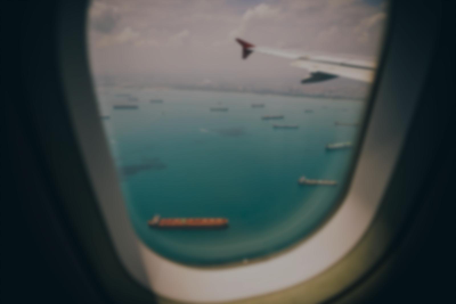 Paysage de bateaux cargos transportants des marchandises à travers un hublot d'avion