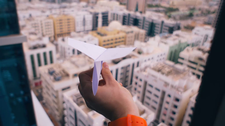 Une main avec un avion en papier au dessus de la ville de Beyrouth au Liban