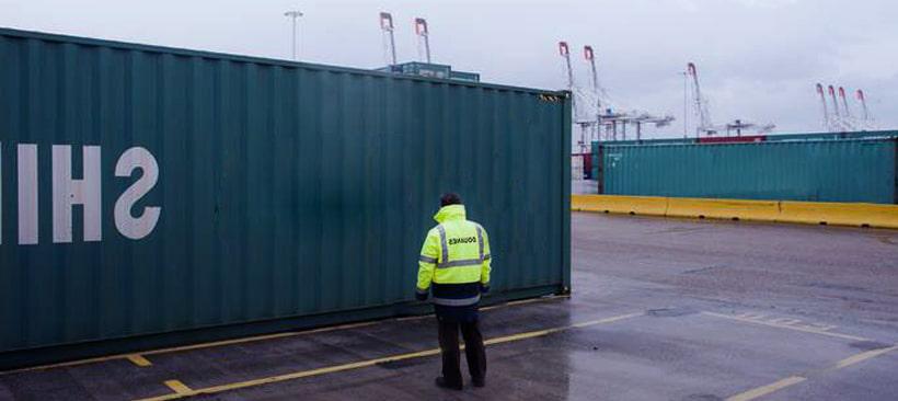 Un docker en tenu de travail devant un conteneur dans un port de pour le fret maritime