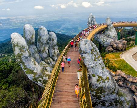 Le pont doré près de Da Nang au Vietnam et des touristes qui circulent dessus